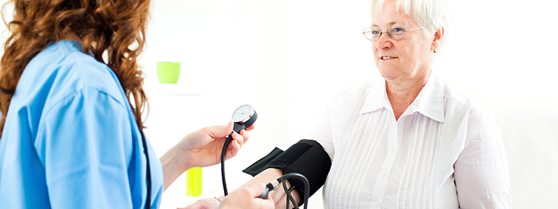 Senior woman at doctors office getting blood pressure check